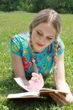 Blondine schreiben in Notizbuch Lizenzfreie Stockfotografie