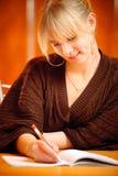 Blondine schreibt zu den Schreibenbüchern Lizenzfreies Stockfoto
