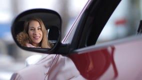 Blondine, senkt das Autofenster, schaut im Seitenspiegel und lächelt 4K langsames MO stock video