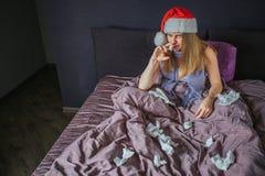 Blondine sitzen auf Bett und leiden Sie benutzt Nasenspray Es gibt viele benutzte Gewebe auf Bett Junge Frau hat lizenzfreie stockfotos