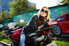 Blondine sitzt über ein rotes Motorrad Stockfotos
