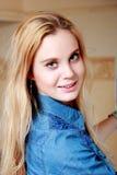 Blondine, stehend im Profil und lächeln an der Kamera, lehnendes forw Lizenzfreie Stockfotografie