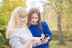 Blondine und Brunette betrachten den Schirm des Telefons Stockbilder