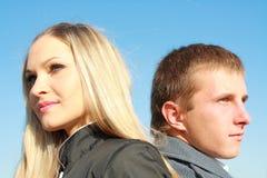 Blondine und Mann stehen auf Hintergrundhimmel Stockfotografie