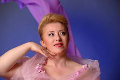 Blondine vierzig Jahre alt im Studioporträt im Rosa Stockfotografie
