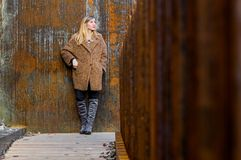 Blondine, welche die rostige Wand bereitsteht Stockfoto