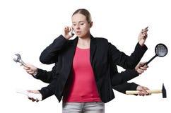Blondinemultitasking auf einem weißen Hintergrund Lizenzfreies Stockfoto