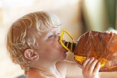 Blondinen behandla som ett barn dricksvatten. Arkivbild