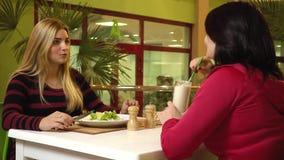 Blondinen har en vegetarisk sallad i kafét för konditionklubban och meddelar med hennes instruktör stock video