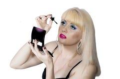 Blondinen lägger på till henne ett smink royaltyfri foto