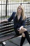 Blondinen lyssnar till musik, parkerar in på en bänk Arkivbilder
