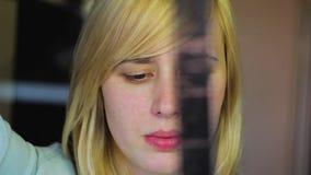 Blondinen med olika ögon undersöker den retro filmen, heterochromia stock video