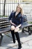Blondinen parkerar in har ett vilasammanträde på en bänk Royaltyfri Fotografi