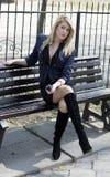 Blondinen parkerar in lyssnar till musiksammanträde på en bänk Fotografering för Bildbyråer