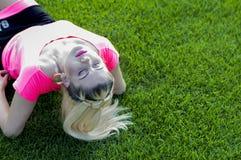 Blondinen som har kastat tillbaka huvudet som ligger på fotbollen fi arkivfoton
