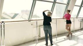 Blondinen tar bilder av en härlig Caucasian brunett i ett vitt rum stock video