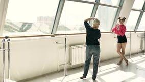 Blondinen tar bilder av en härlig Caucasian brunett i ett vitt rum lager videofilmer