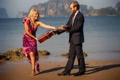 blondinen tar gitarren från gitarrist på stranden arkivfoton