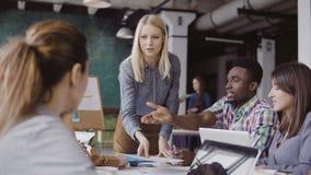 Blondineteamleiter, der dem Mischrasseteam von jungen Kerlen Richtung gibt Kreatives Geschäftstreffen im modernen Büro Stockfotos