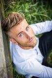 Blondish, синь наблюдала молодой человек на деревянной загородке стоковое фото rf