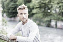 Blondish, синь наблюдала молодой человек усмехаться реки стоковые фото