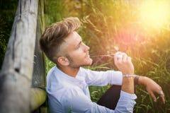 Blondish, синь наблюдала молодой человек на деревянной загородке стоковое фото