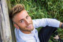 Blondish, синь наблюдала молодой человек на деревянной загородке стоковые фотографии rf