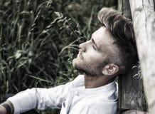 Blondish, синь наблюдала молодой человек на деревянной загородке стоковое изображение