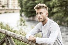 Blondish, синь наблюдала молодой человек рекой стоковое фото