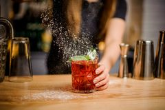 Blondy barmaid finishes preparation of cocktail by adding a bitter of powdered sugar. Feat blondy barmaid finishes preparation of red alcoholic cocktail in Stock Photo