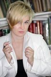 Blondy on books background. Blondy looking ahead on books background Royalty Free Stock Photos