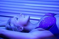 Blondy en solarium Imagenes de archivo