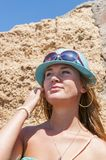 Blondy girl with sunglasses and blue hat on the beach. Tenerife Royalty Free Stock Image