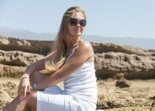 Blondy girl in white with sunglasses on the beach. Tenerife Royalty Free Stock Photos