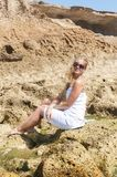 Blondy girl in white with sunglasses on the beach. Tenerife Stock Photo