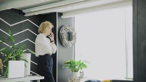 Blondy kvinna som talar p? telefonen Arbetekvinna som talar på mobil på kontoret stock video