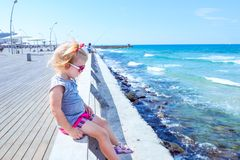 Free Blondy Little Baby Girl 2-3 Year Old In Pink Sunglasses Sitting Alone On Wooden Sea Railing On The Seafront Of Tel Aviv. Looking A Royalty Free Stock Images - 114163409