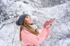 Blondy-Mädchen-Fangschneeflocken im Winterwald lizenzfreie stockbilder