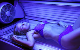 Blondy in solarium. Beautiful young woman tanning in solarium Stock Image