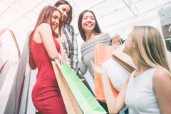 Blondy is standing a little bit lower on escalator that her friends. She is looking at them. Friends are looking down to. Blondie and smiling. They look happy royalty free stock image