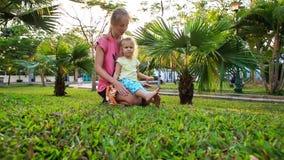 Blondyn córki Macierzysty kucnięcie na trawie wśród palm w parku zbiory wideo