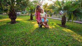 Blondyn córki Macierzysty kucnięcie na trawie wśród palm w parku zdjęcie wideo