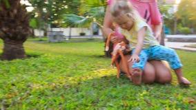 Blondyn córki Macierzysty kucnięcie na trawie wśród palm w parku zbiory