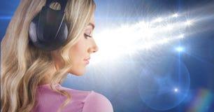 Blondyn dziewczyny listenning muzyka z hełmofonami z powrotem fotografia z błękitnym tłem Zdjęcia Royalty Free