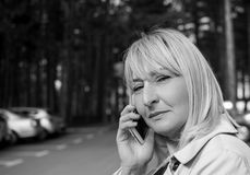 Blondyn kobieta opowiada na telefonie komórkowym i ono uśmiecha się Obrazy Royalty Free