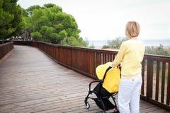 Blondyn kobieta spaceruje dziecka w frachcie Obraz Stock