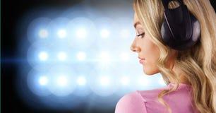 Blondyn kobiety listenning muzyka z hełmofonami z powrotem fotografia Obrazy Royalty Free