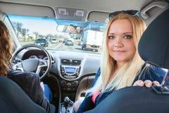 Blondyn młoda kobieta pasażerski przyglądający z powrotem gdy jadący samochód Zdjęcia Royalty Free