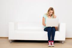 Blondynek kobiety siedzi na leżance z poduszką Obraz Stock