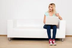 Blondynek kobiety siedzi na leżance z poduszką Zdjęcia Stock